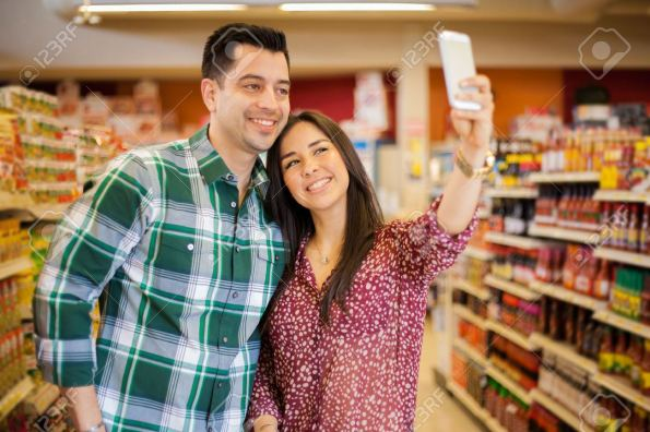 26683975-Happy-young-couple-taking-a-selfie-with-a-smart-phone-while-shopping-at-the-supermarket-Stock-Photo